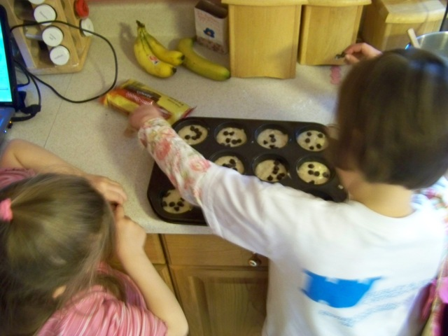 Karis and Kristi sprinkling the chocolate chips on top of the muffins