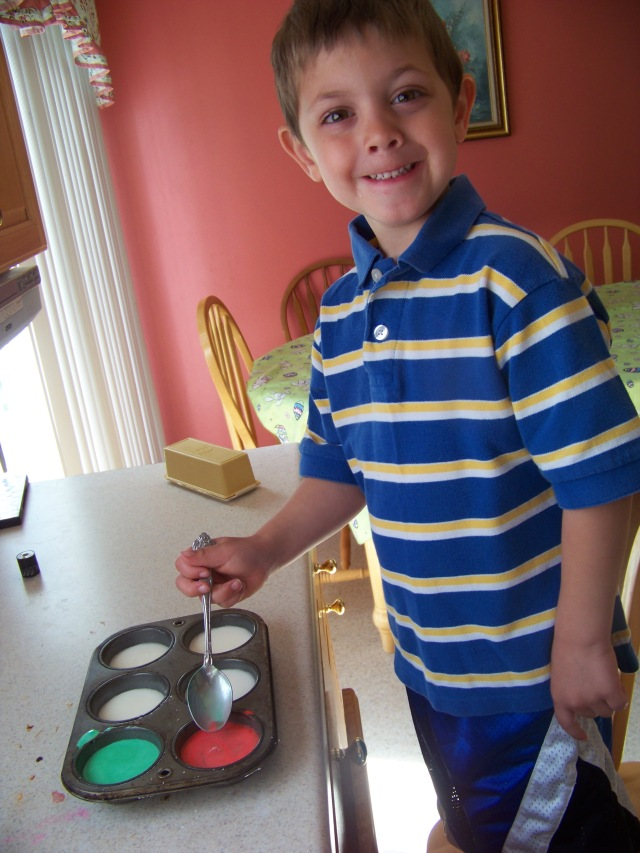 Joshua helping stir the paint.