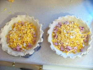 The onion, cheese, and ham in the pie plates.