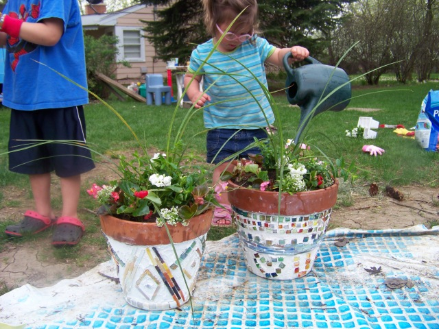"Kiley ""helping"" water the flowers."